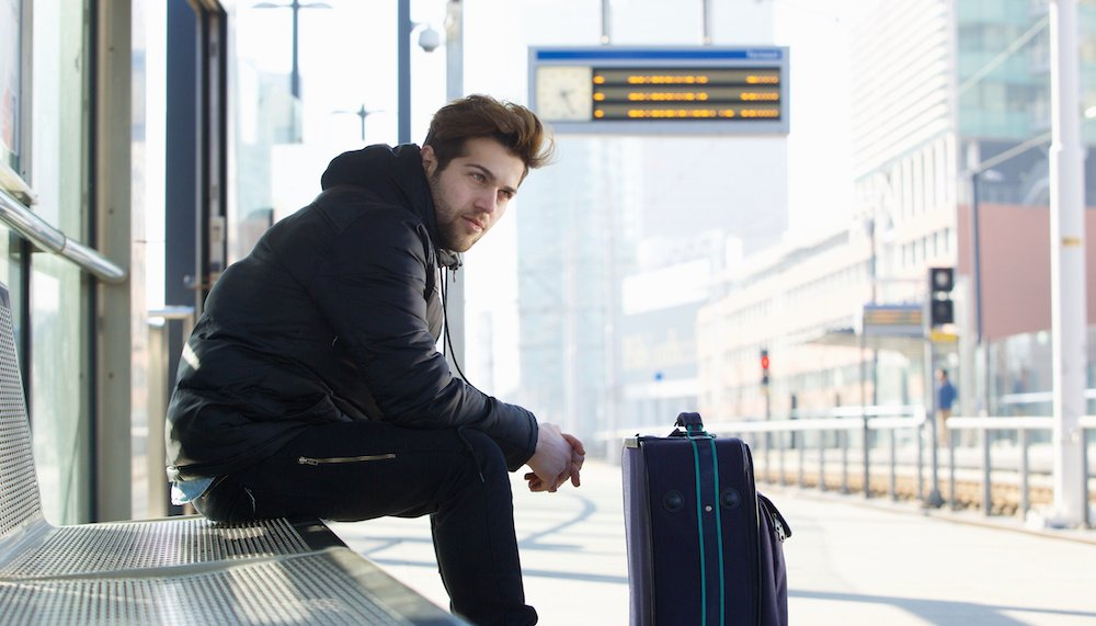 Young man waiting for train with suitcase travel bag