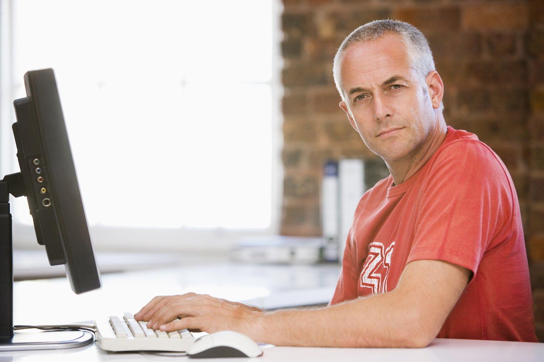 Man at PC Looking at Camera 1500×1000